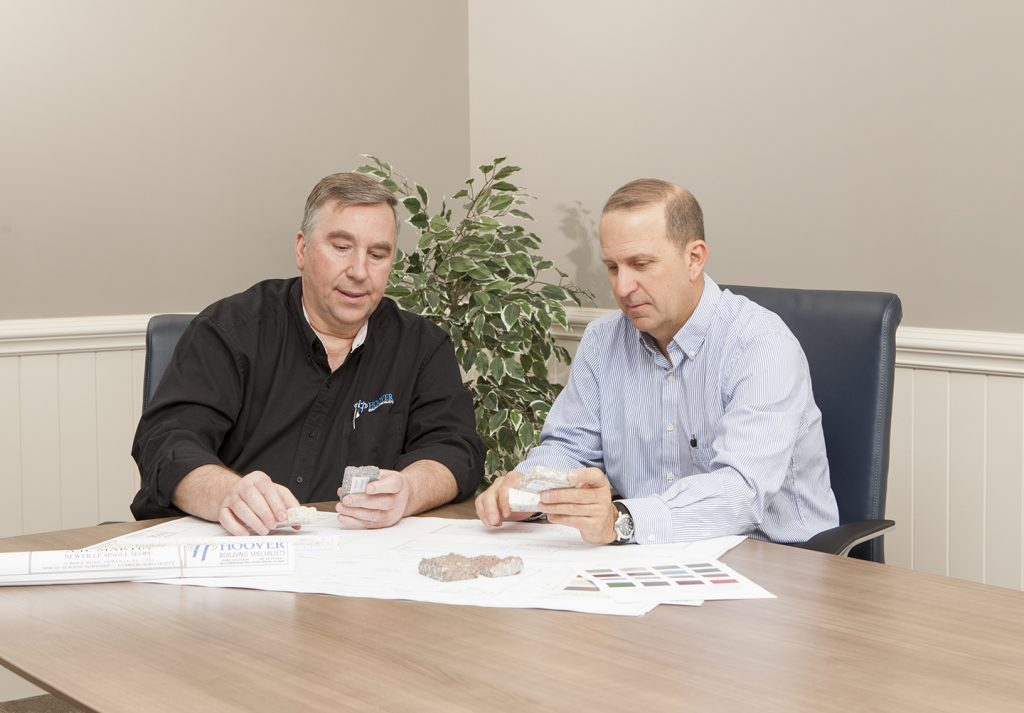 two men comparing building materials
