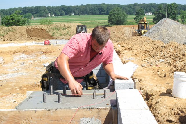 construction worker laying building foundation for new steel building